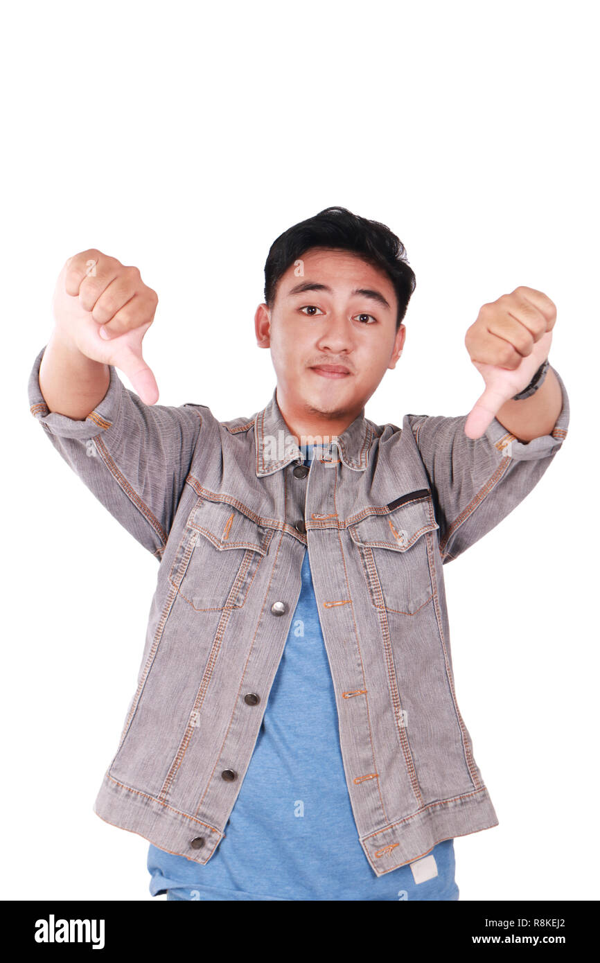 Photo image portrait of a cute young Asian man doing mocking gesture and showing two thumbs down isolated on white - Stock Image