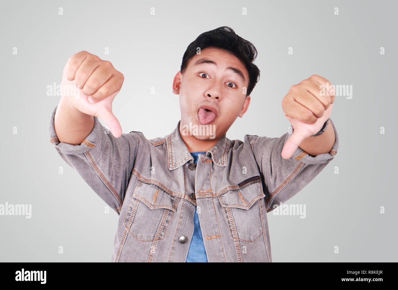 Photo image portrait of a cute young Asian man doing mocking gesture with tongue out and showing two thumbs down - Stock Image