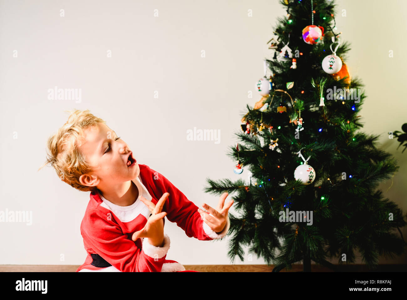 Toddler Christmas Tree Costume.Toddler With Santa Claus Costume Making Faces Next To