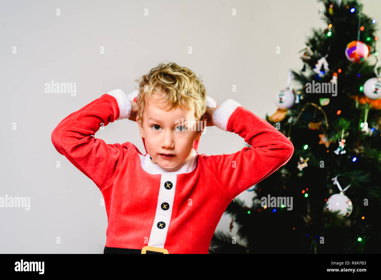 Toddler Christmas Tree Costume.Handsome And Blond Toddler Wearing Santa Costume Next To