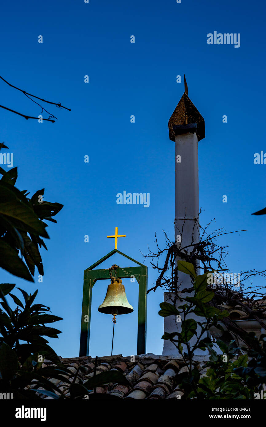 Greek Orthodox monastery roof details, brass bell on stand, golden cross and tall chimney over red tiled roof in clear blue sky spring day - Stock Image