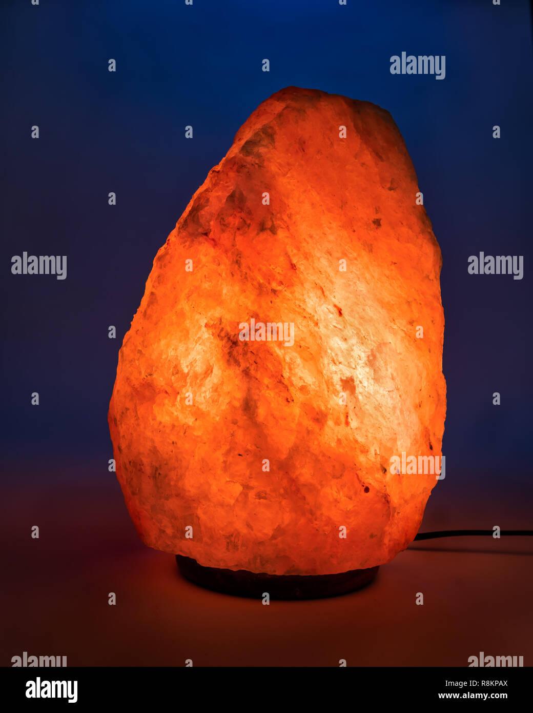 Large Himalayan Salt Lamp Glowing Against Plain Blue
