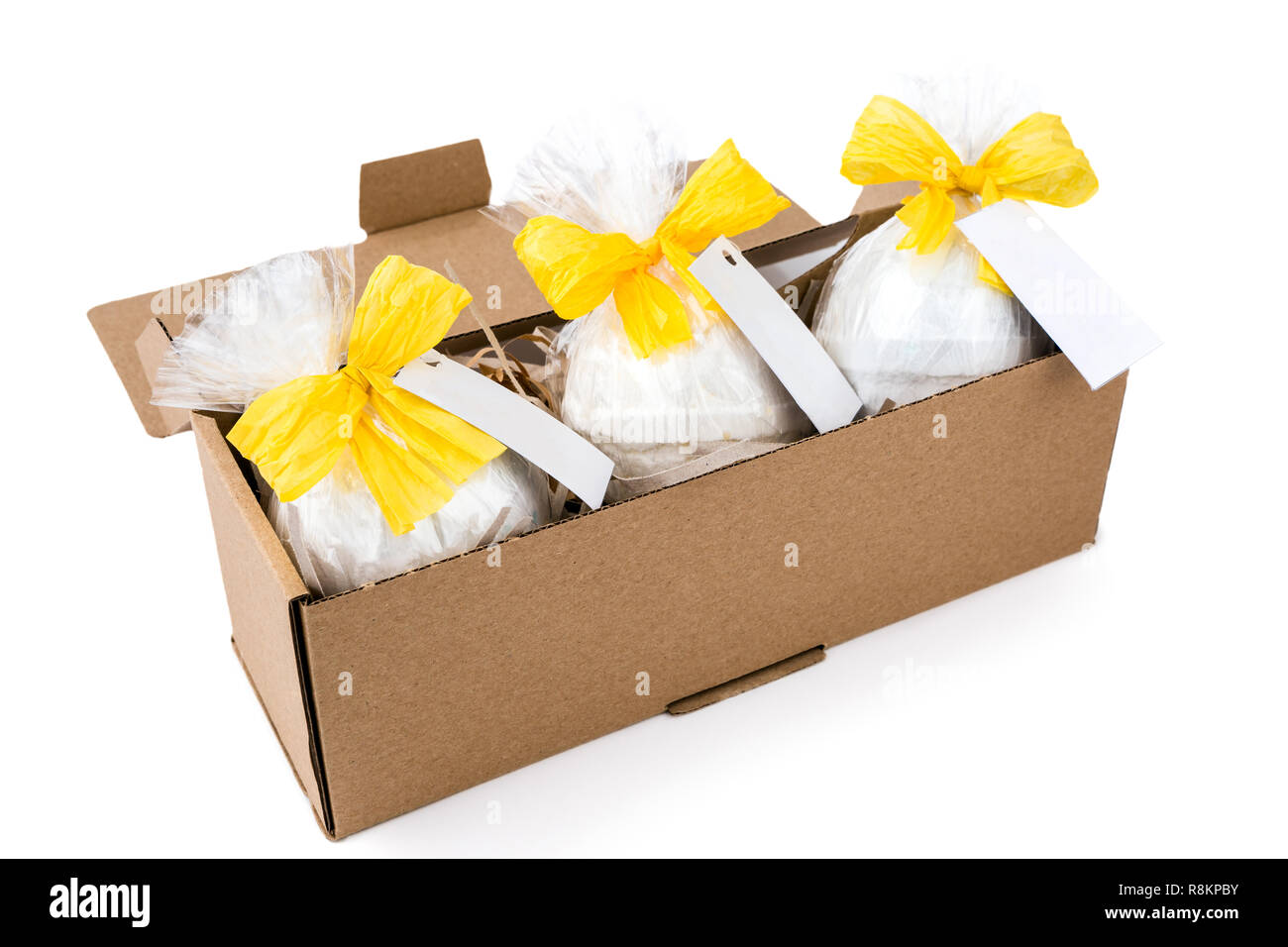 Gift set with cellophane wrapped  aromatherapy bath bombs, decorated with yellow bows on the white background - Stock Image