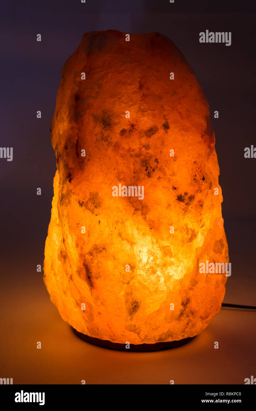 Large Himalayan Salt Lamp Glowing Against Plain Background