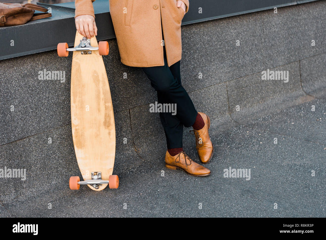 cropped view of businessman in coat holding penny board - Stock Image