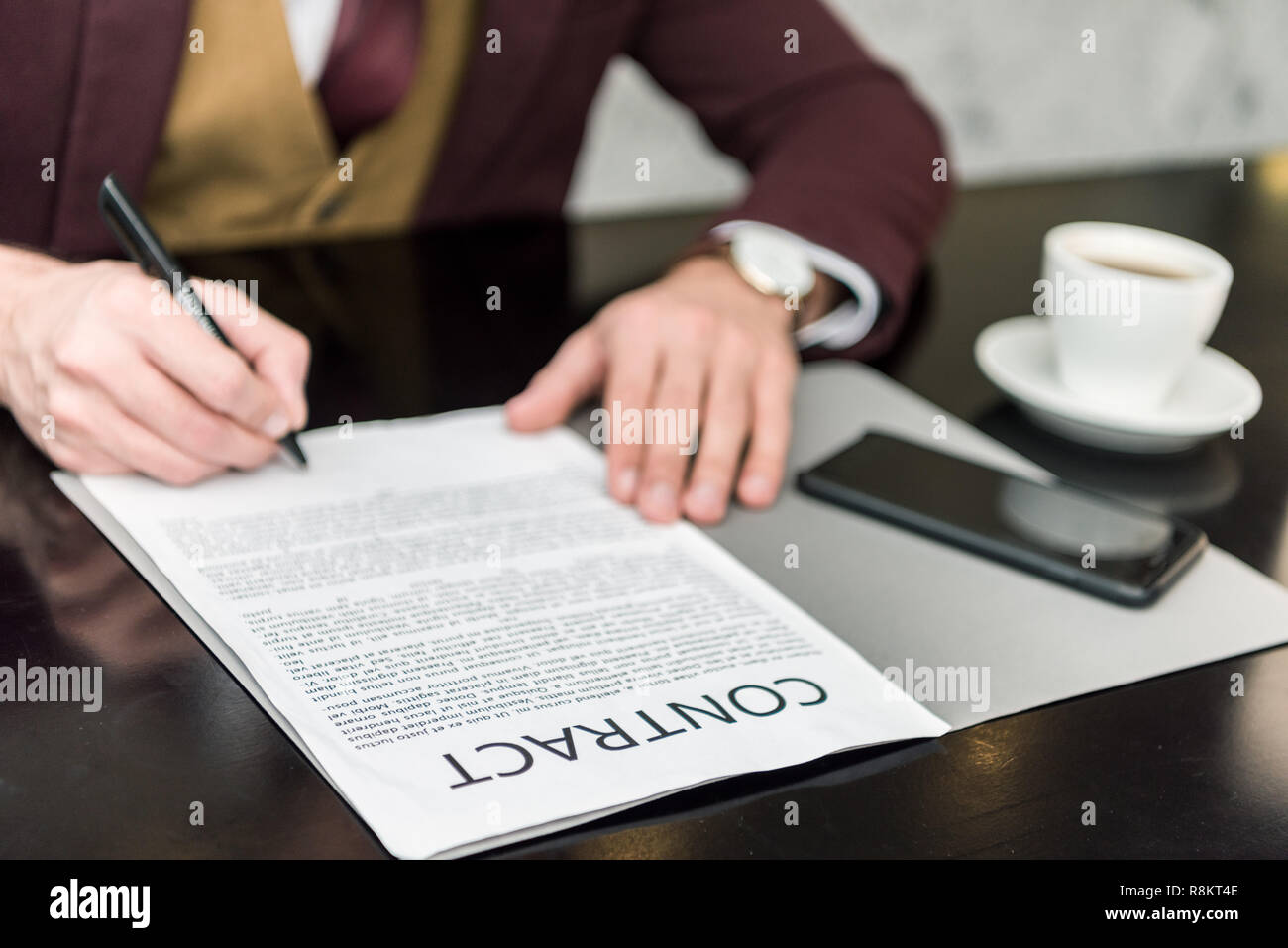 cropped view of businessman in formal wear sitting at table and signing contract Stock Photo
