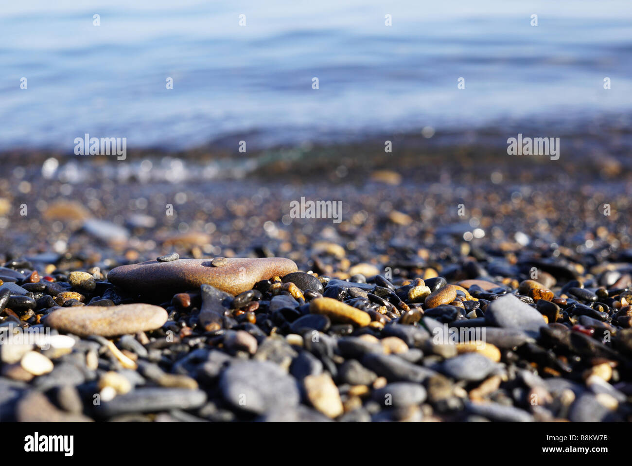 Pebbles on the shore in focus and in the background the surf and waves. Sea surf and waves visible behind sea pebbles. Far East of Russia, Vladivostok - Stock Image