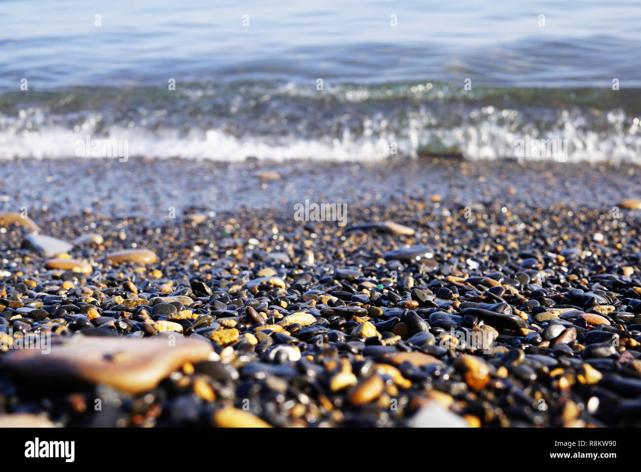 On the seashore there are many small stones of different shapes. sea surf and waves visible behind sea pebbles. Far East of Russia, Vladivostok - Stock Image