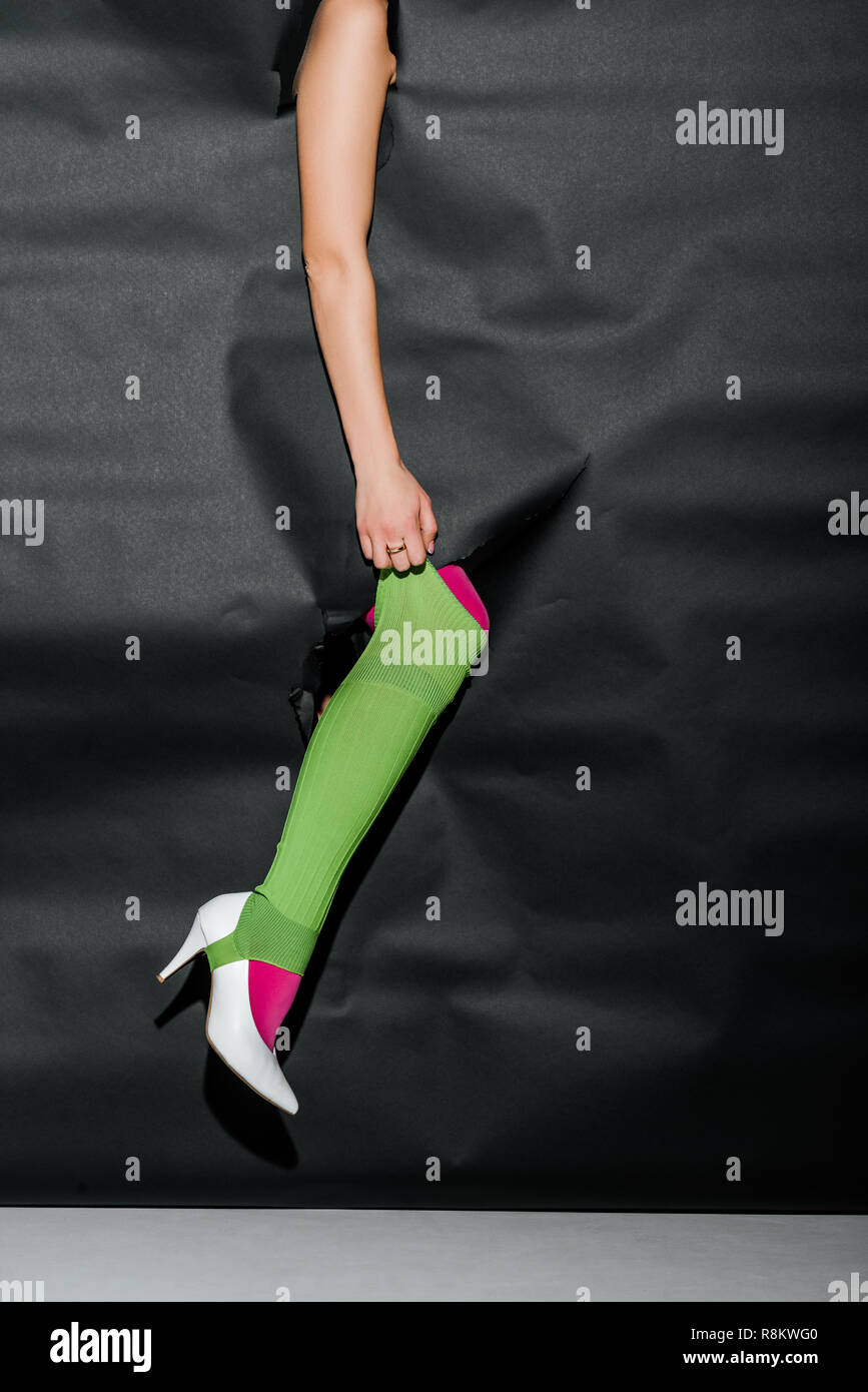 9efb0de4b09ca cropped image of girl showing leg in pink tights and white high heel  through black paper