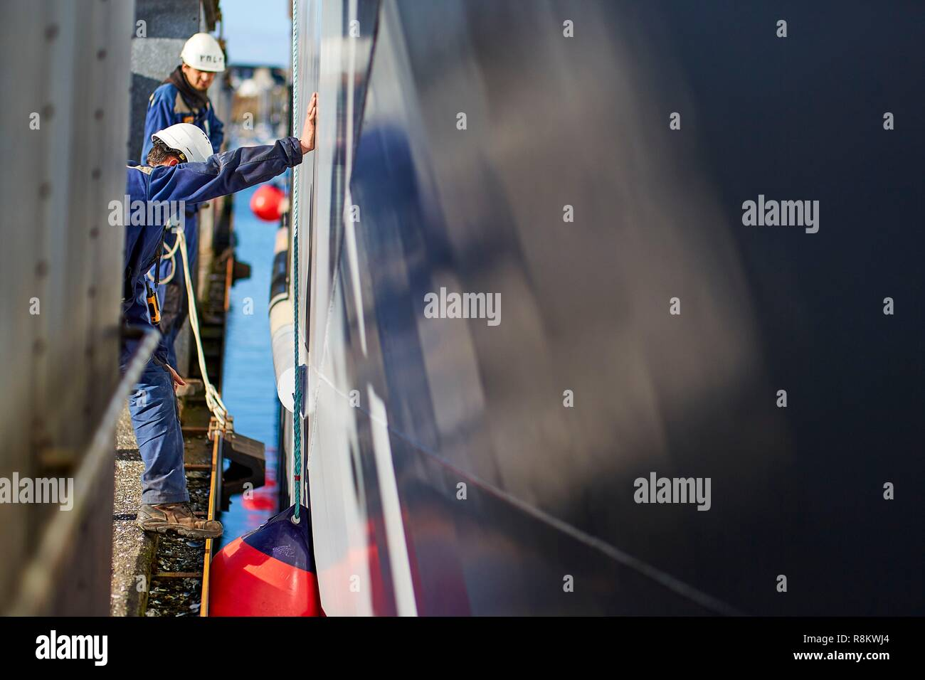 France, Finistere, Concarneau, Workers pushing the hull of a ship during its launch - Stock Image