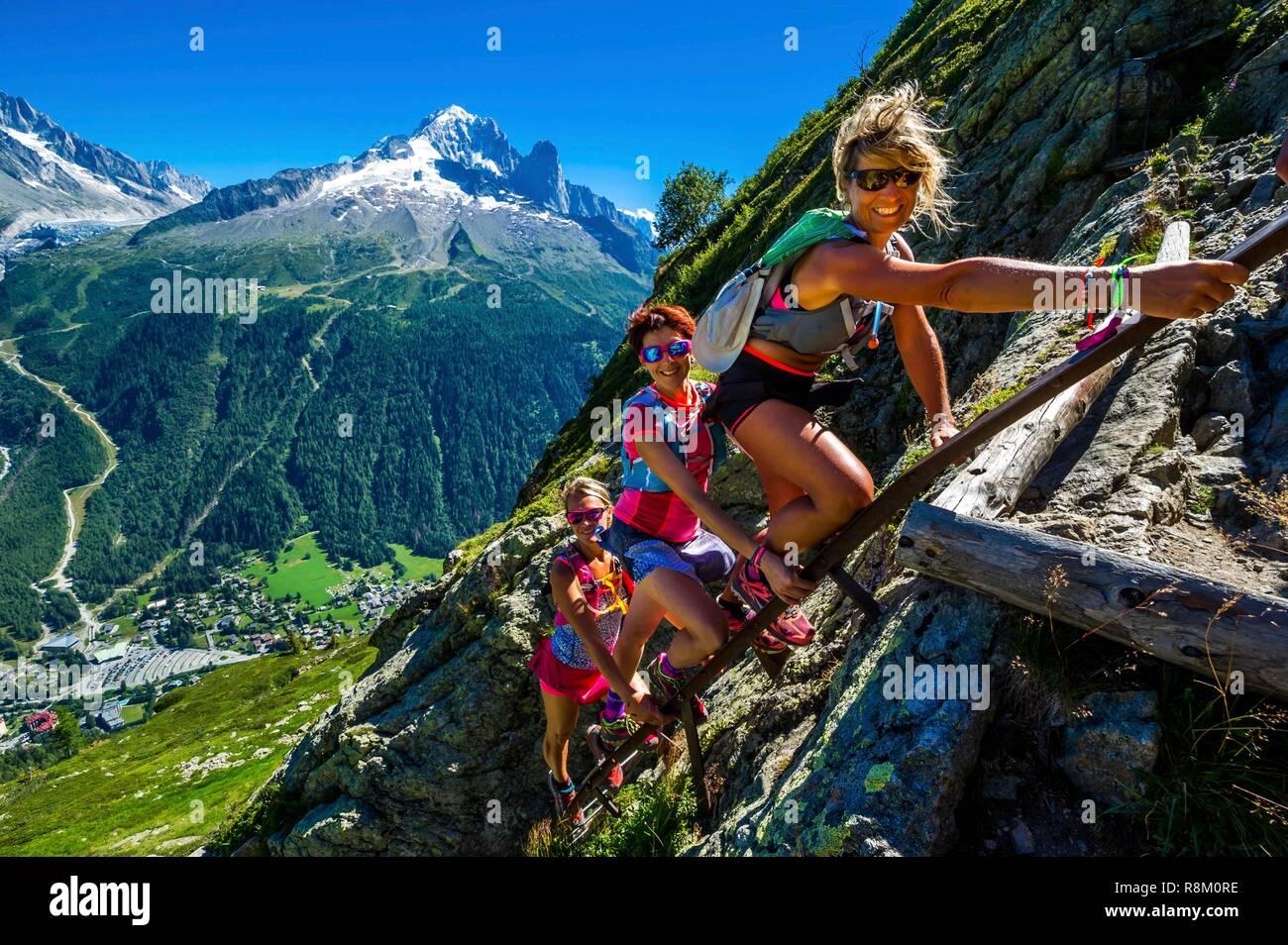 France, Haute-Savoie, Argentière, Aiguilles Rouges range, Tour du Mont Blanc, iron ladder of Aiguillette d'Argentière trail, Ceramik Girls team, female trail runners, with Aiguille Verte and Les Drus in the back Stock Photo