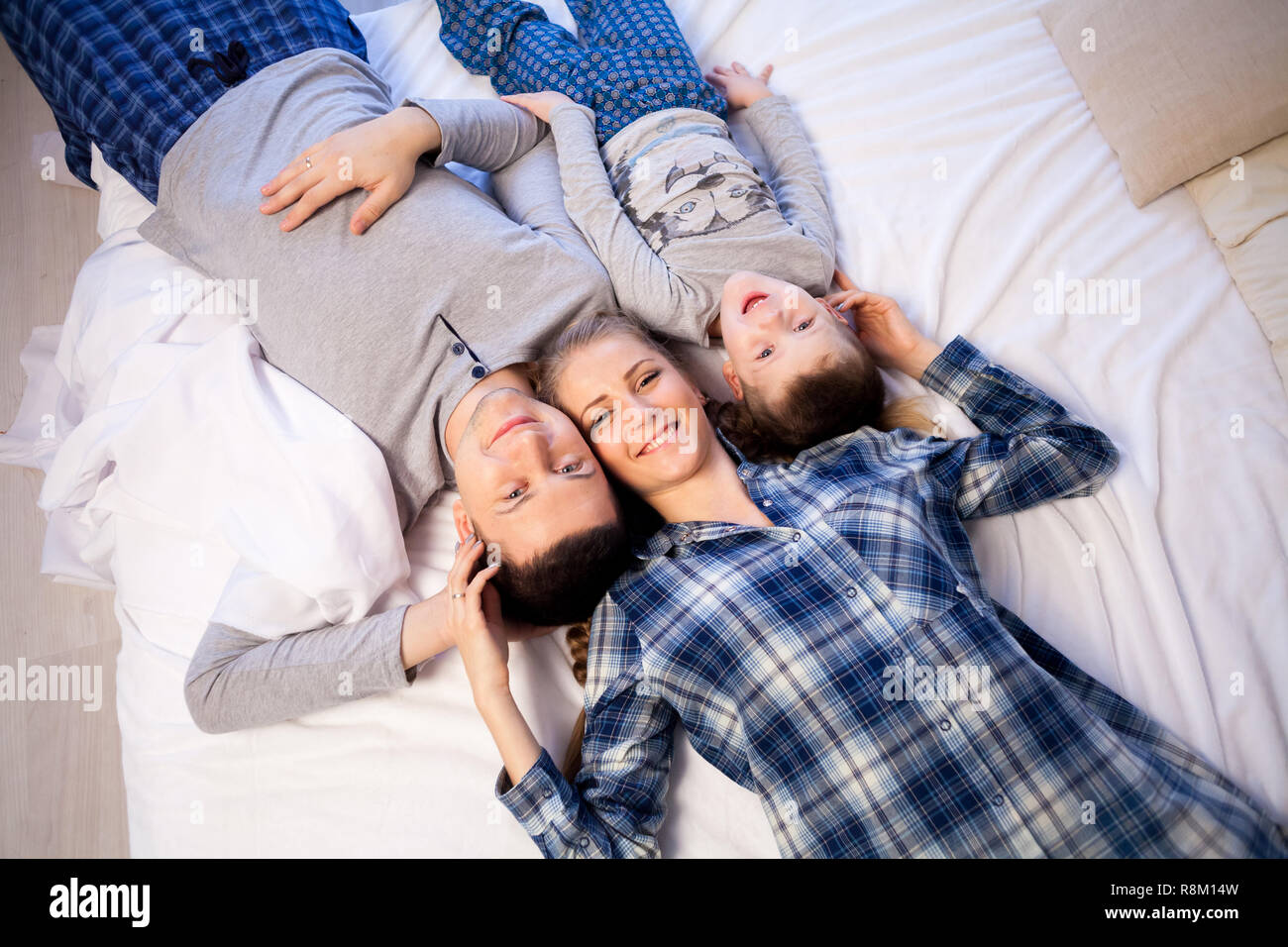 The family morning in the bedroom on the bed mom dad son