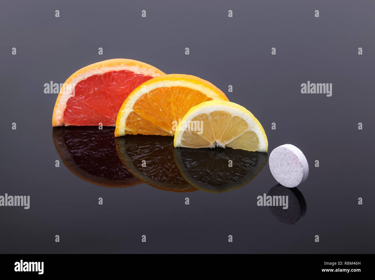 Grapefruit ,Orange and Lemon slices and a vitamin tablet .Natural vitamin C versus synthetic vitamins. - Stock Image