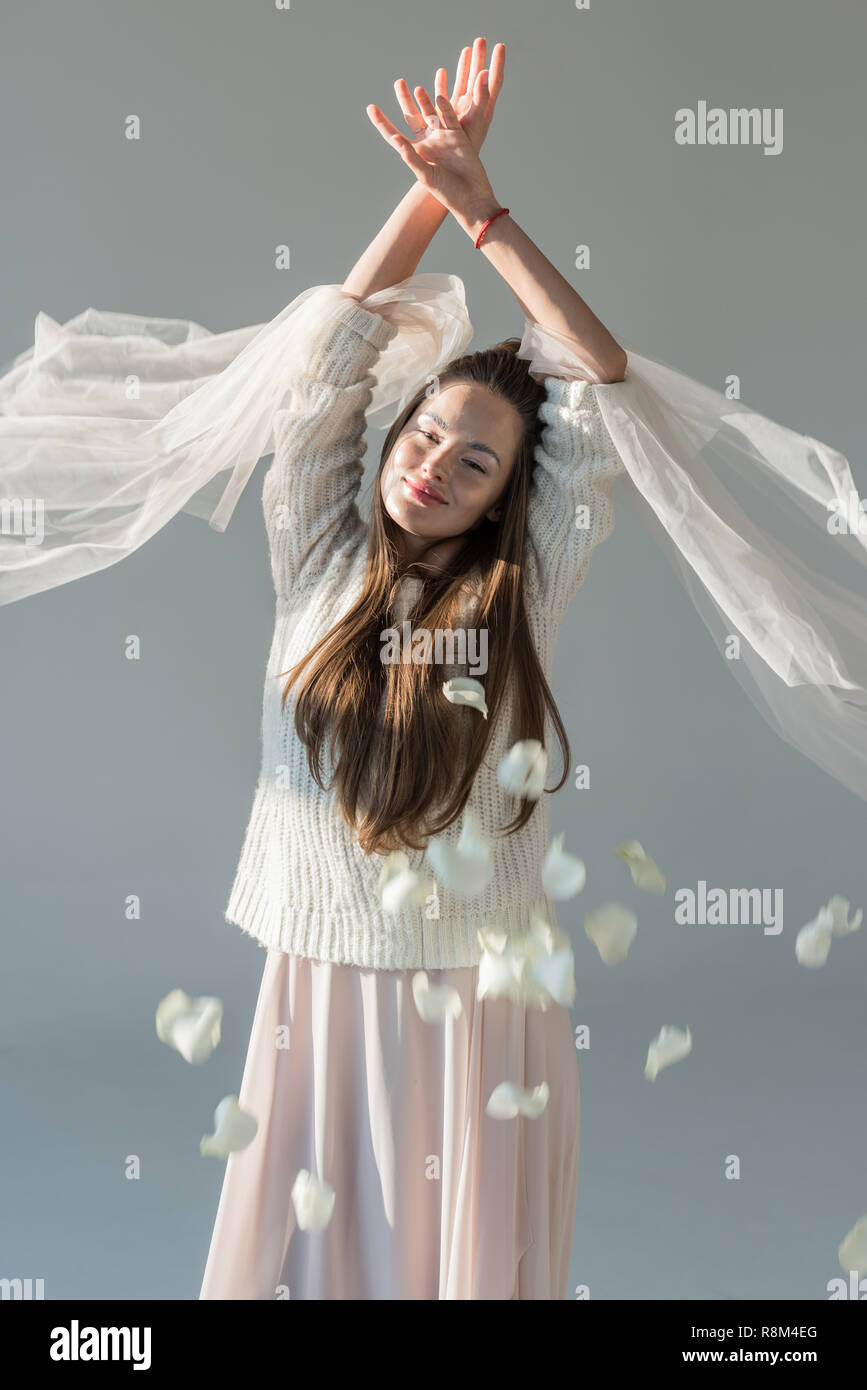happy attractive woman in fashionable winter outfit standing under falling petals isolated on grey - Stock Image