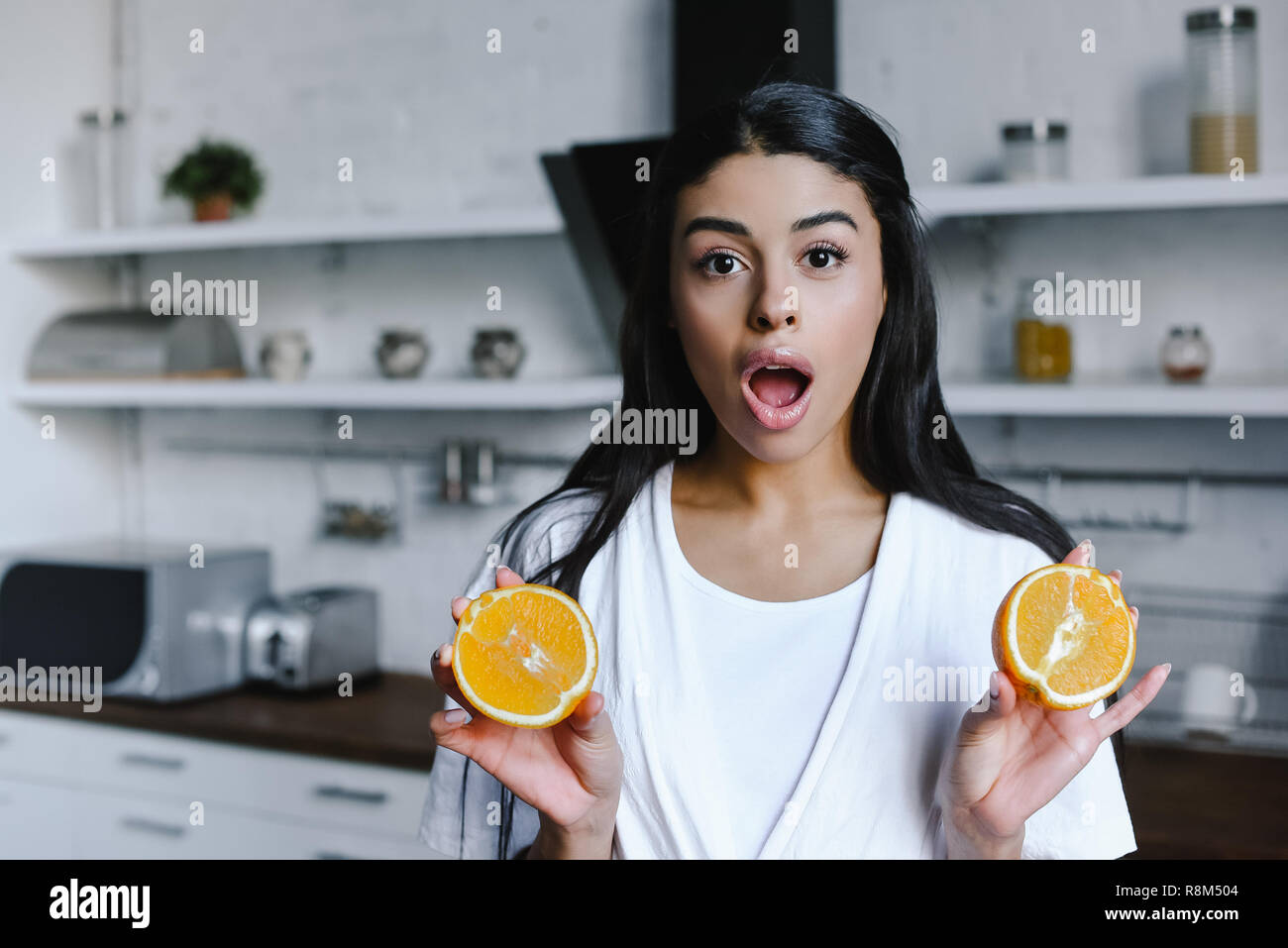 shocked mixed race girl in white robe holding cut orange and looking at camera in morning in kitchen Stock Photo