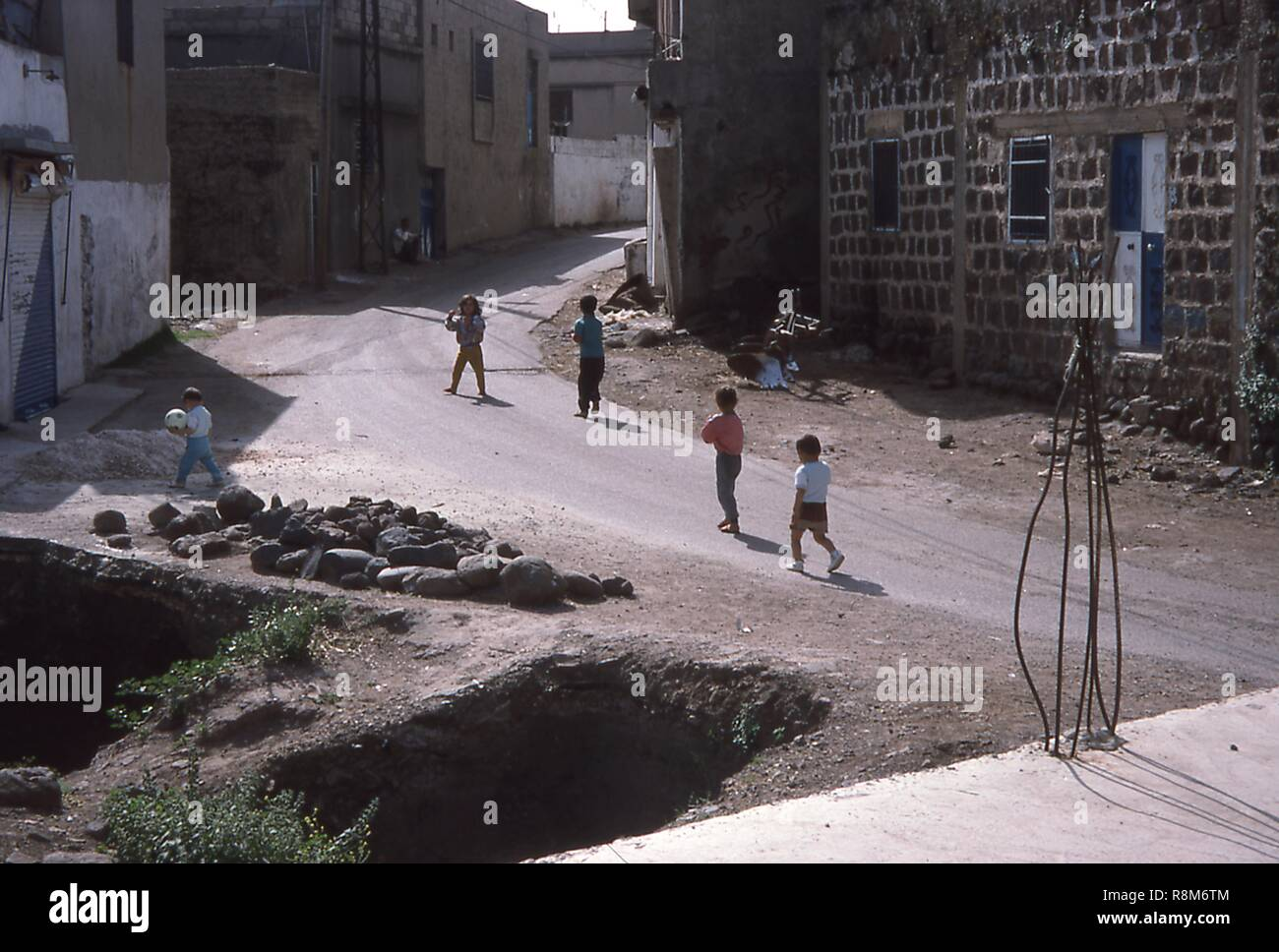 Scene of children playing football (soccer) on a dusty street in Qalaat al-Madiq, Syria, June, 1994. () - Stock Image
