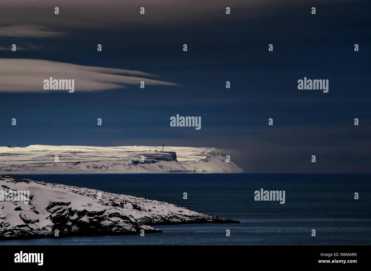 Frosty night landscape the Arctic Ocean. Northern severe cold nature cliffs. Dark deep blue water and sky, white clouds, black rocky coast shore. The Barents Sea, Kola peninsula Teriberka, Russia. - Stock Image