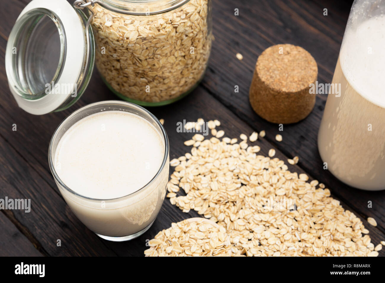 Glass of vegan, dairy-free oat milk and oats on a dark wooden background with texture. Concept of a vegan diet. - Stock Image