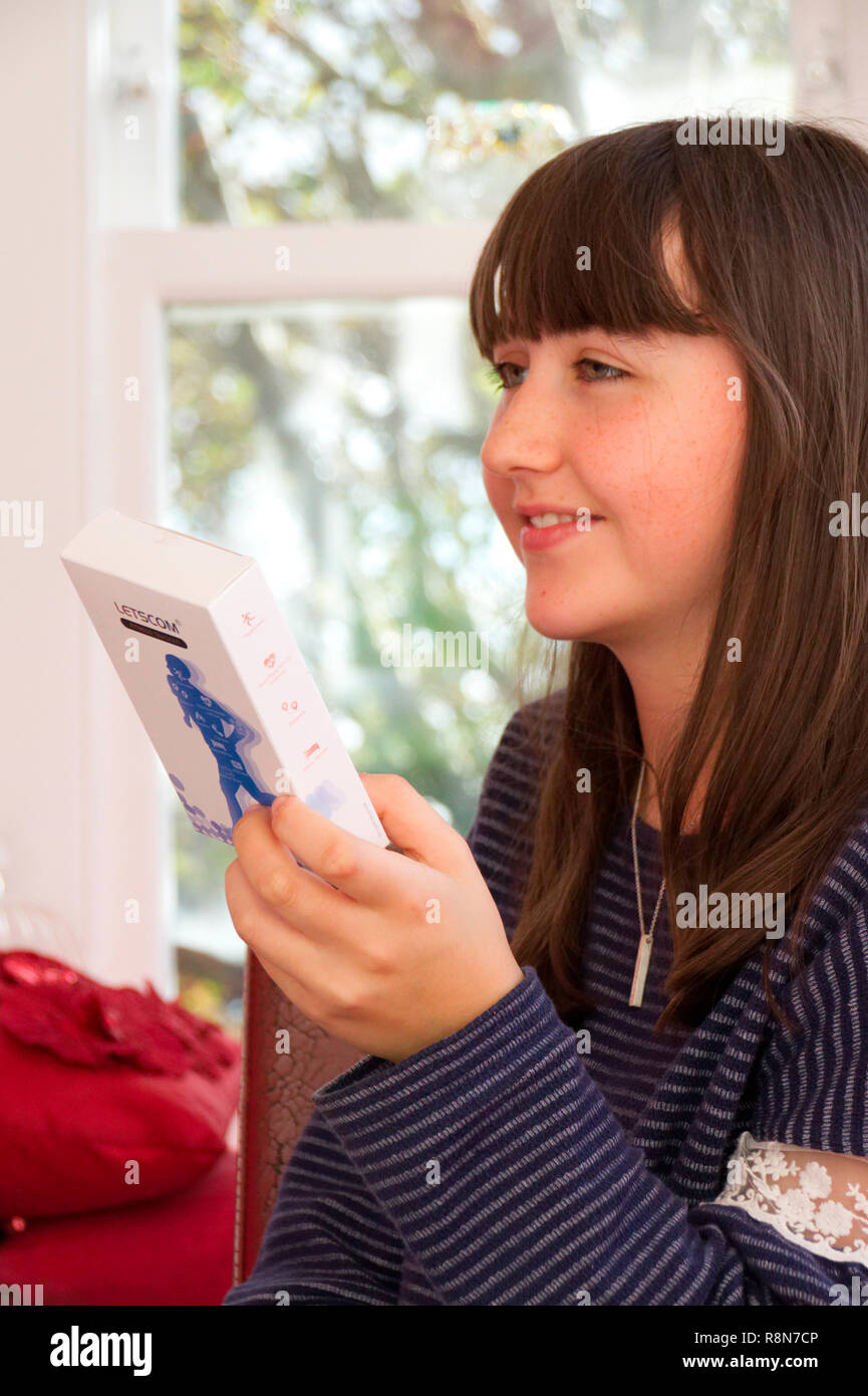 Contented 13 year old girl with present - Stock Image