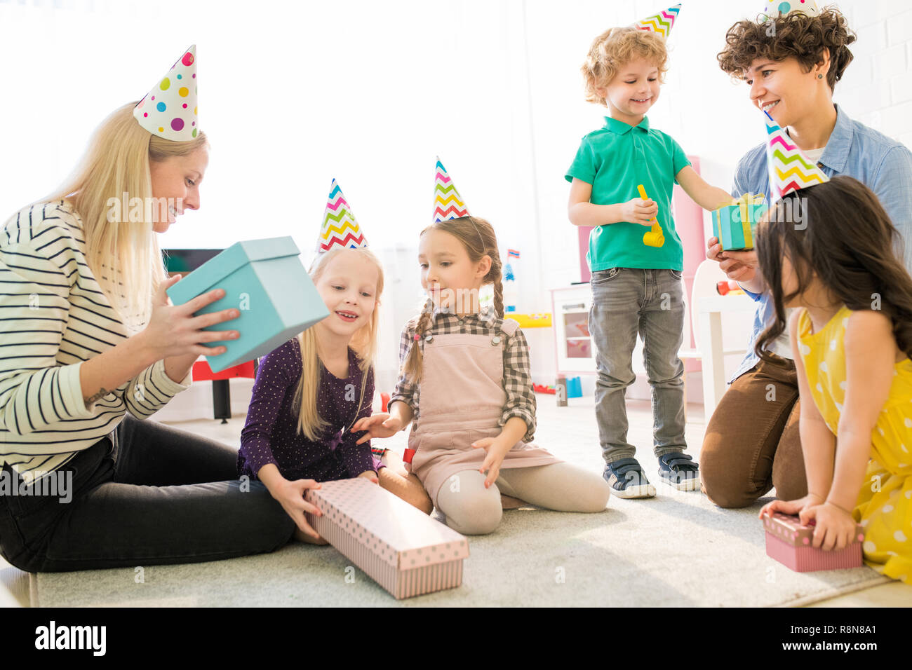 Mothers and children guessing what is inside of gift box - Stock Image