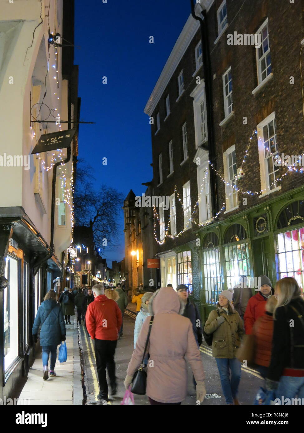 Christmas shoppers enjoy the festive atmosphere and street lights of the popular winding streets through The Shambles in York city centre; Dec 2018 - Stock Image