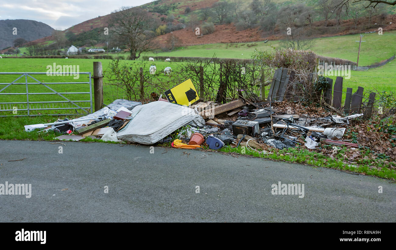 In a quiet peaceful country lane a fly tipper has disposed of rubbish and waste by the hedge and gate of a farmers field - Stock Image