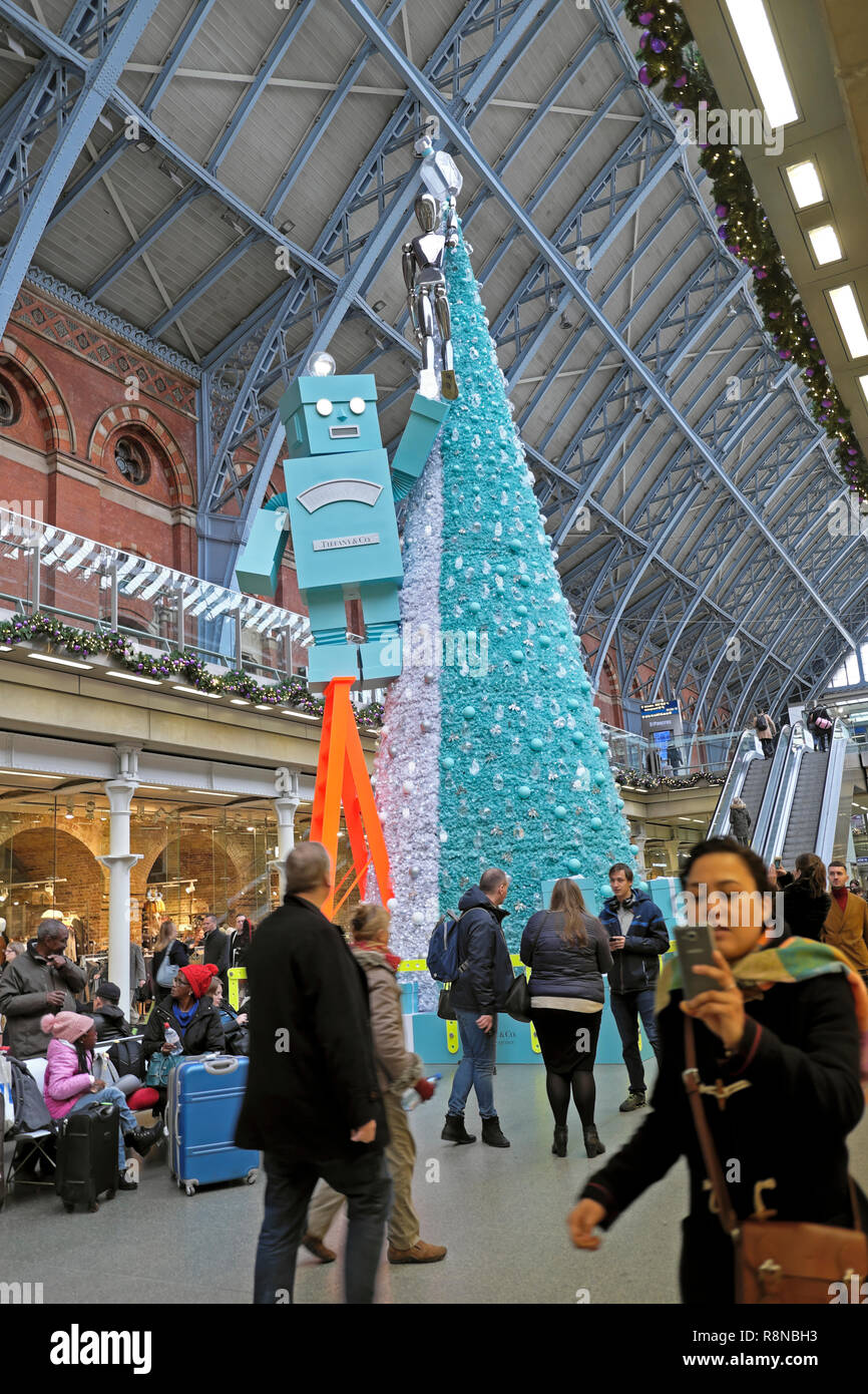 Tiffany & Co Christmas tree and robot & woman taking selfie in shopping mall area at St Pancras International Railway Station London UK  KATHY DEWITT Stock Photo