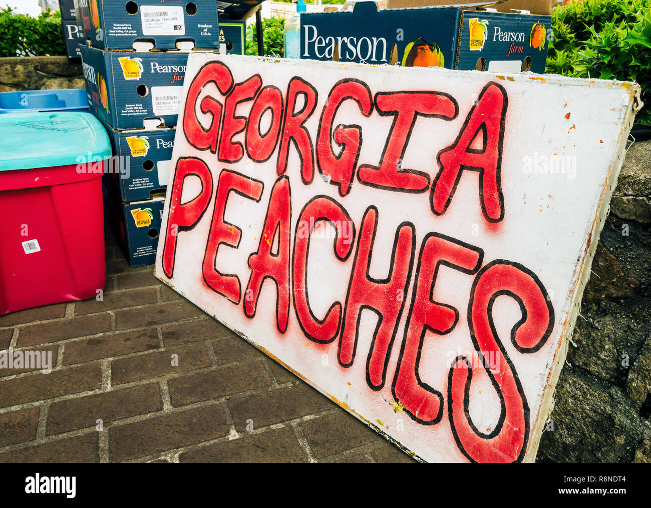Fresh Georgia peaches, grown in Fort Valley, Georgia at Pearson Farm, are stacked for sale at the Tucker Farmers Market in downtown Tucker, Georgia. Stock Photo
