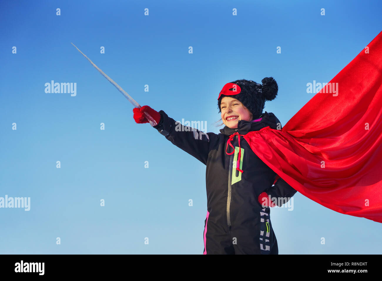 Funny little girl playing power super hero. - Stock Image