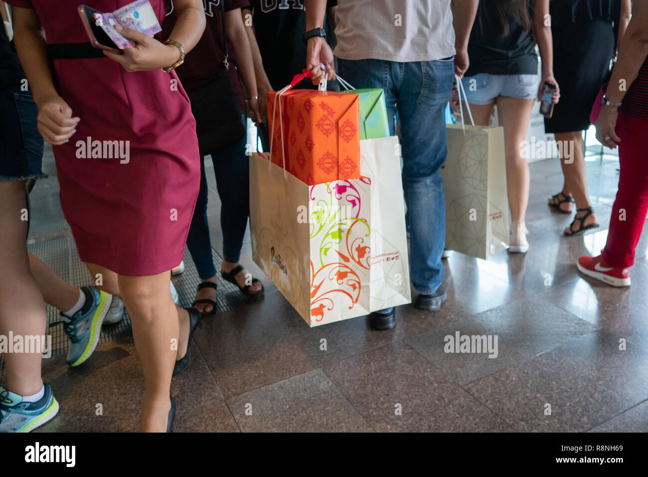 A man carrying xmas presents near to a money holding money,within a bust department store,Cebu City,Philippines - Stock Image