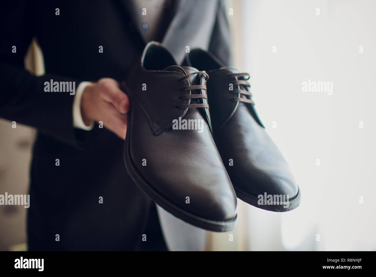 Groom's morning. Wedding accessories. Shoes. The groom ties hoelaces on his shoes - Stock Image