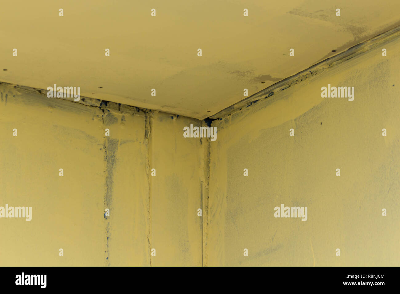 An iron corner at the junction of the walls with seams of an incomprehensible color. Texture background Stock Photo