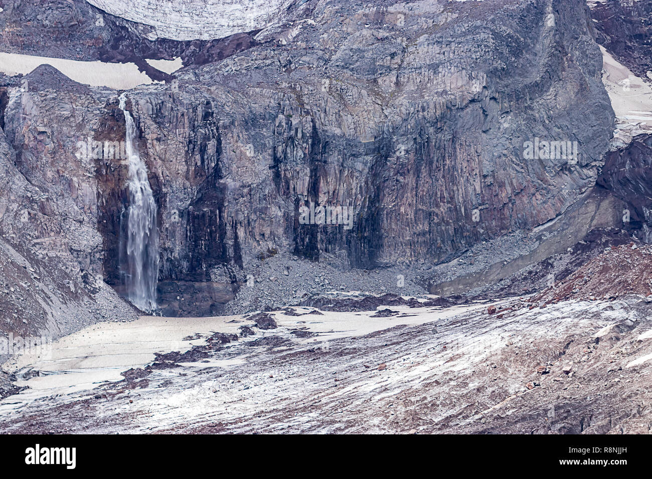 waterfall crashing down into valley from glacial fields near mount rainier - Stock Image