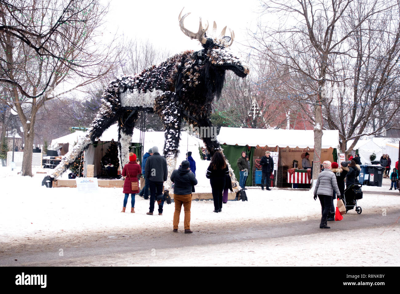 Moose art statue made from 90% recycled materials standing over the crowd at Holidazzle Winter Event in Loring Park. Minneapolis Minnesota MN USA - Stock Image