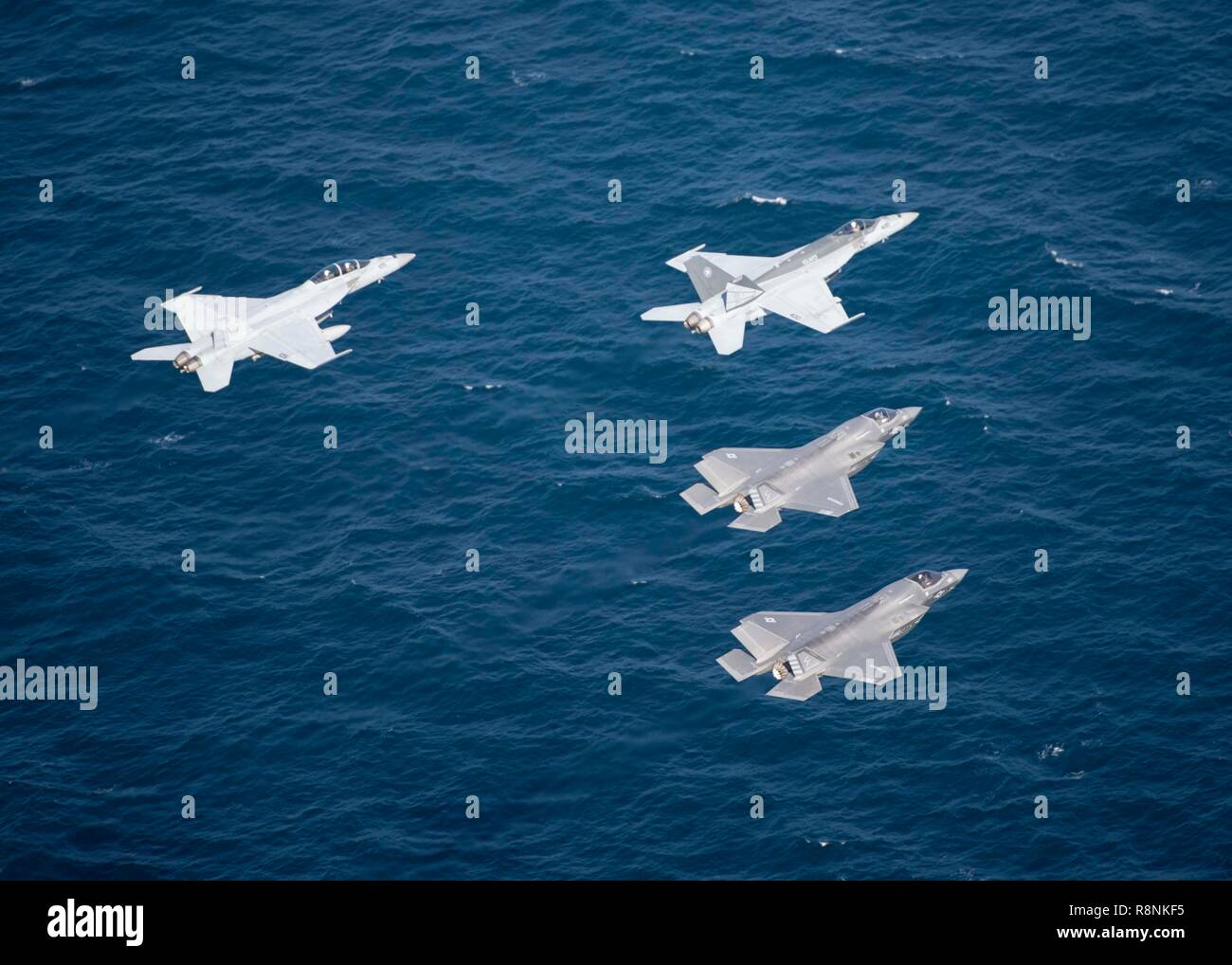 U.S. Marine Corps F-35B Lightning II stealth fighters fly in formation with Navy F/A-18 Super Hornets during a patrol from the Nimitz-class aircraft carrier USS John C. Stennis December 14, 2018 in the Arabian Sea. - Stock Image