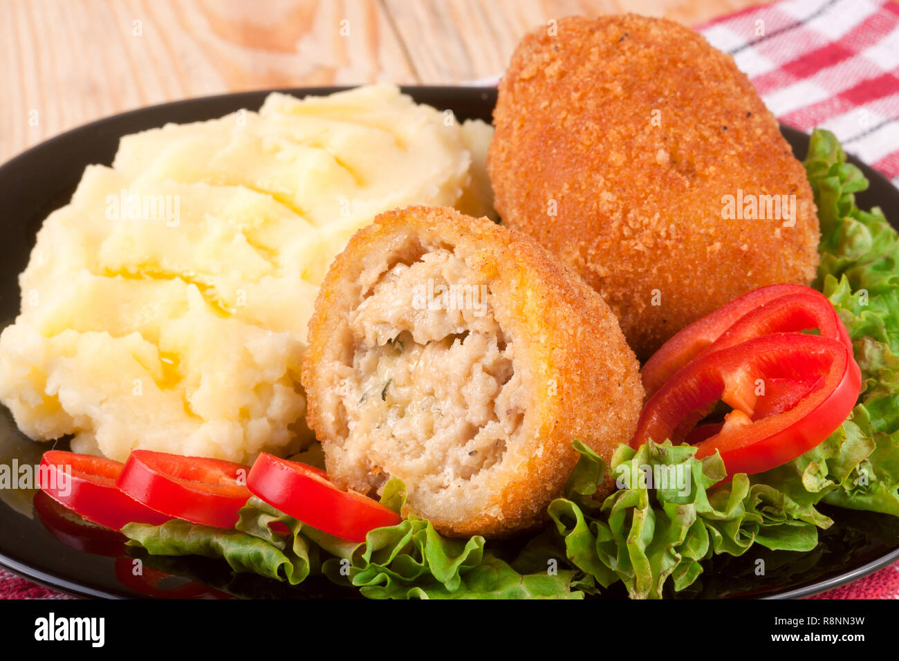 three fried breaded cutlet with mashed potatoes lettuce on a black plate and wooden background - Stock Image