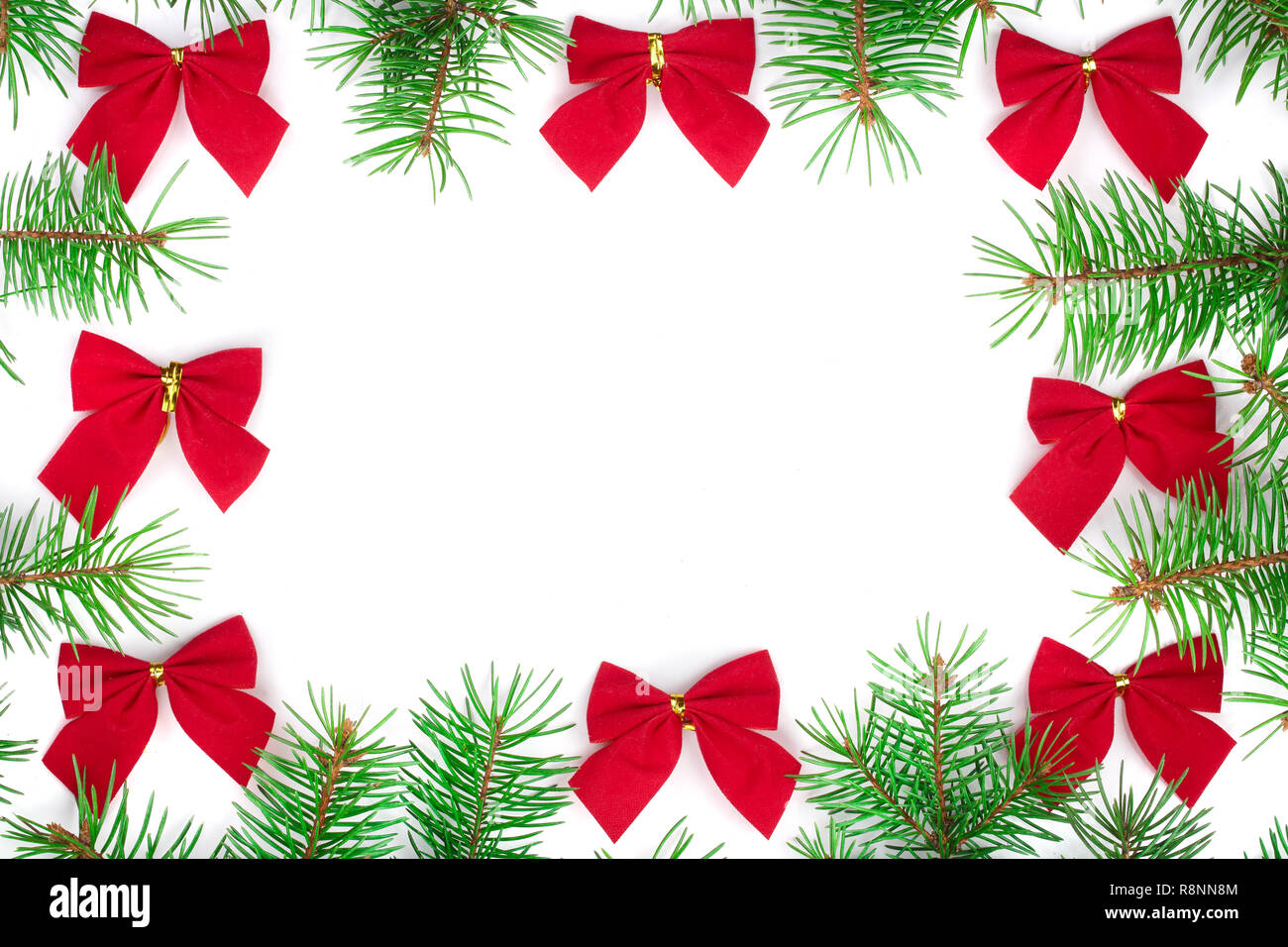 Christmas Frame of Fir tree branch with red bow isolated on white background with copy space for your text. Top view - Stock Image
