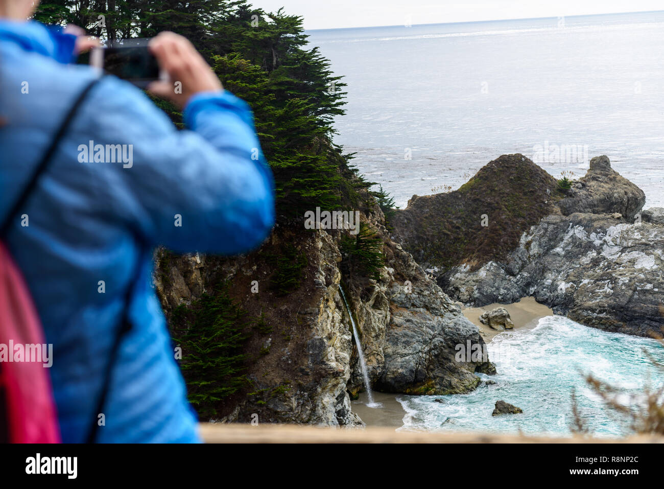A tourist take a picture of the McWay Falls cove - Stock Image