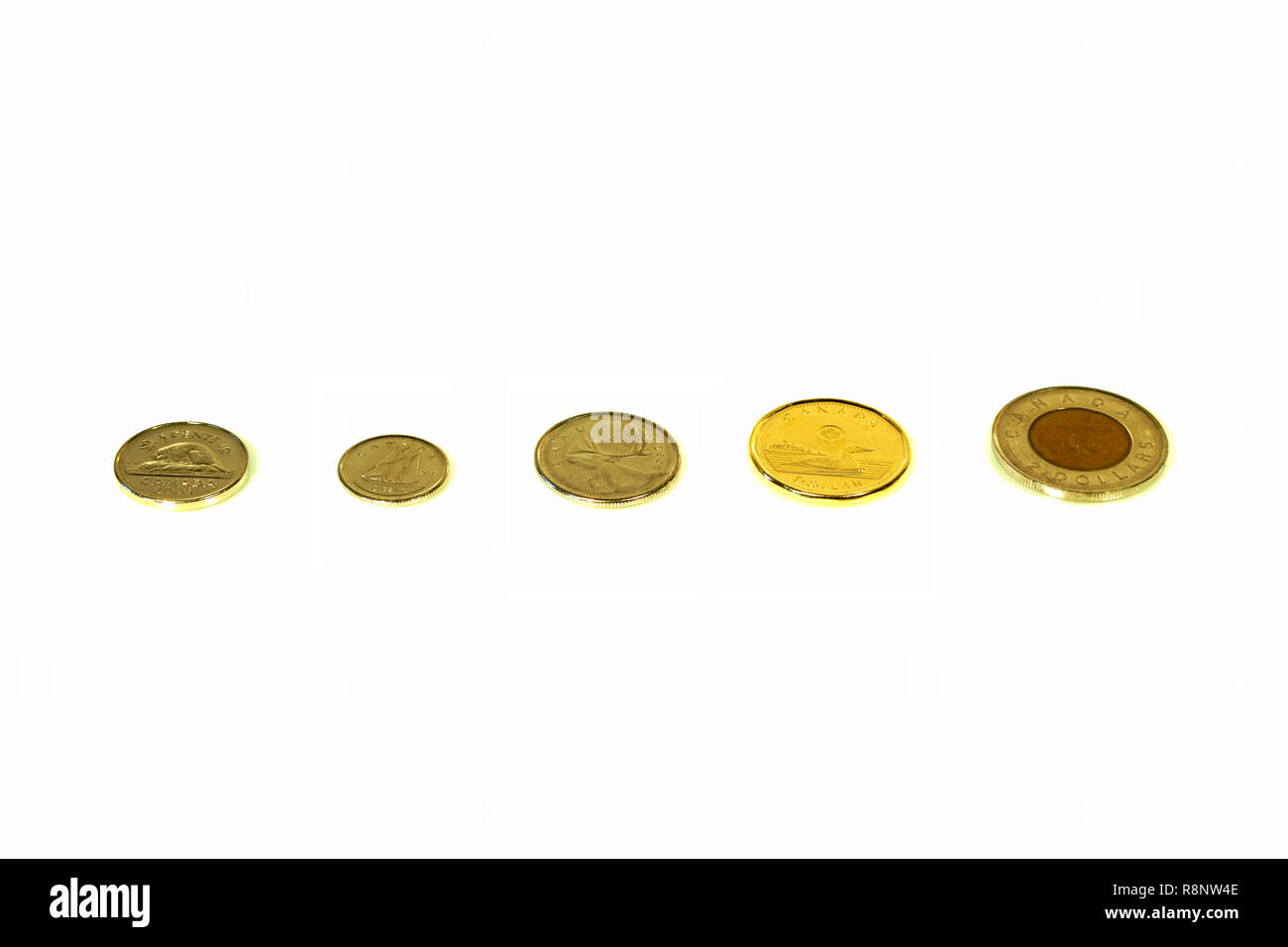 Montreal, Quebec, Canada / Dec, 16th 2018 : Spare change of canadian metal pieces isolated on white. Nickel, dime, quarter, one, two dollar pieces. - Stock Image