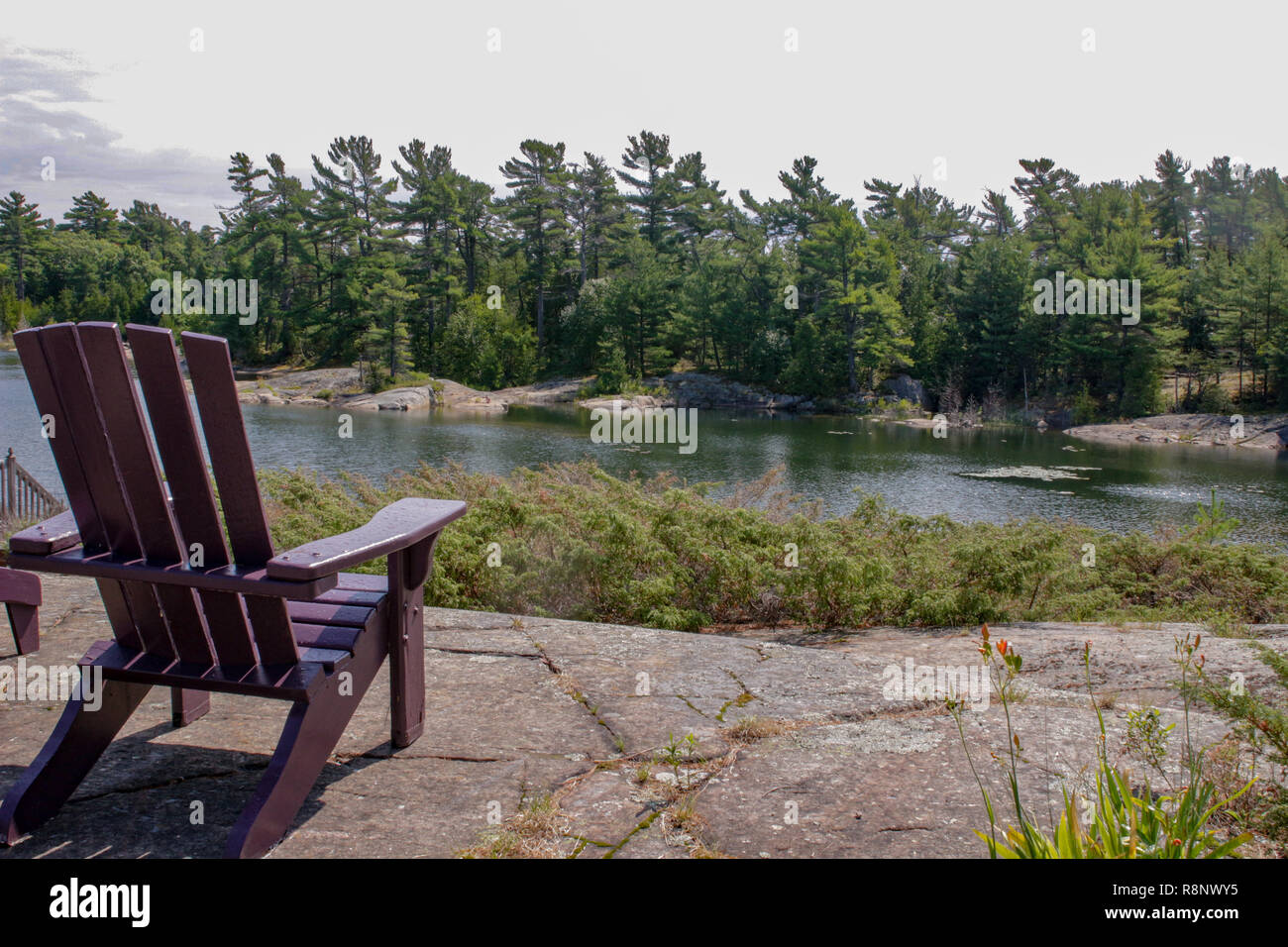 Two black Muskoka chairs sitting on a wood dock facing a lake. Across the calm water is a white cottage nestled among green trees. Canada flag is visible - Stock Image
