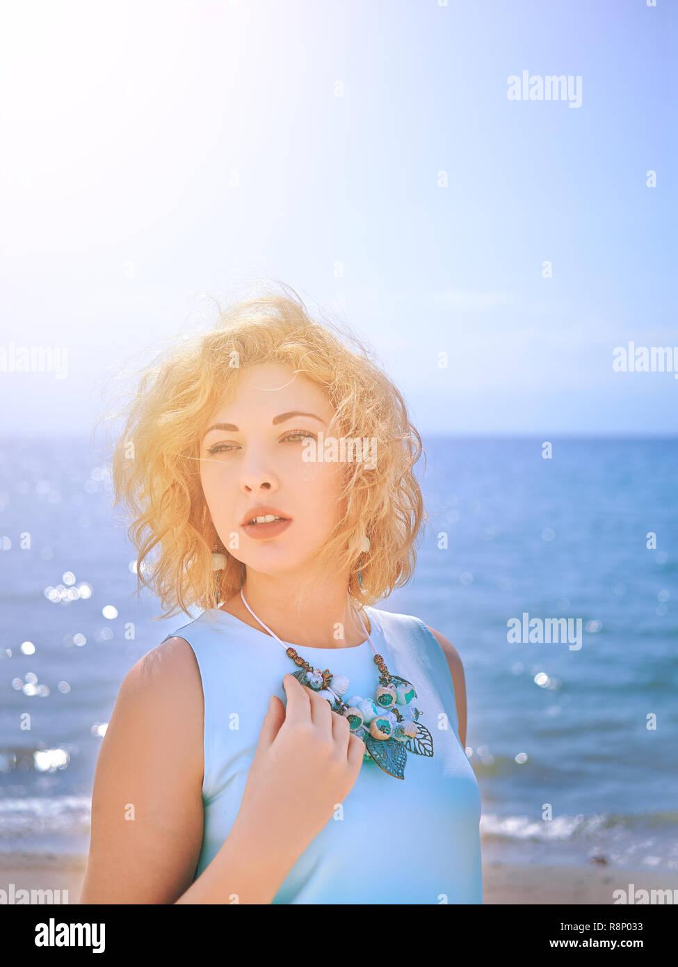 Sensuality blondy woman in cyan dress on the beach - Stock Image