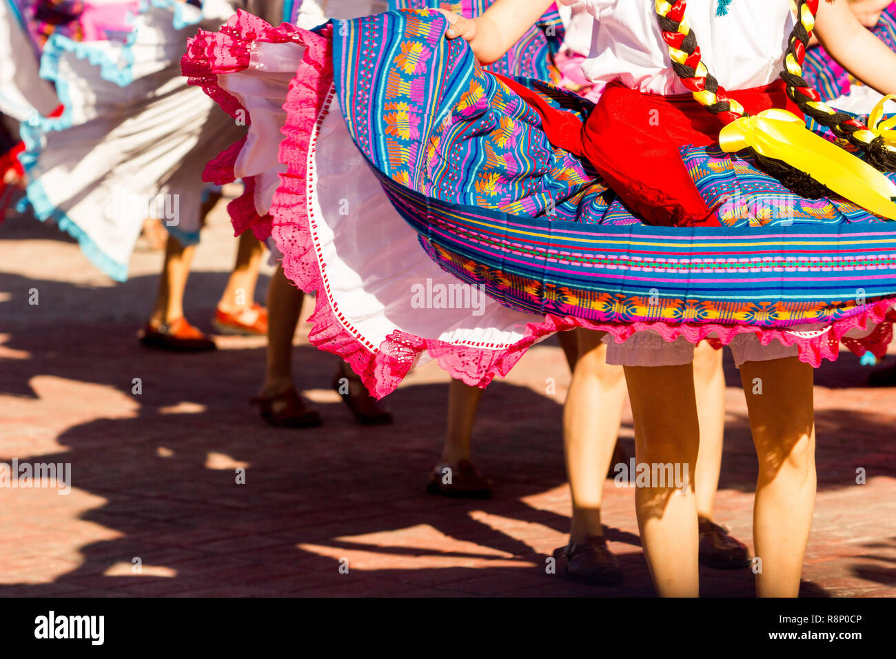dance crew of female dancers wearing colorful traditional dresses dance waving her long skirts - Stock Image