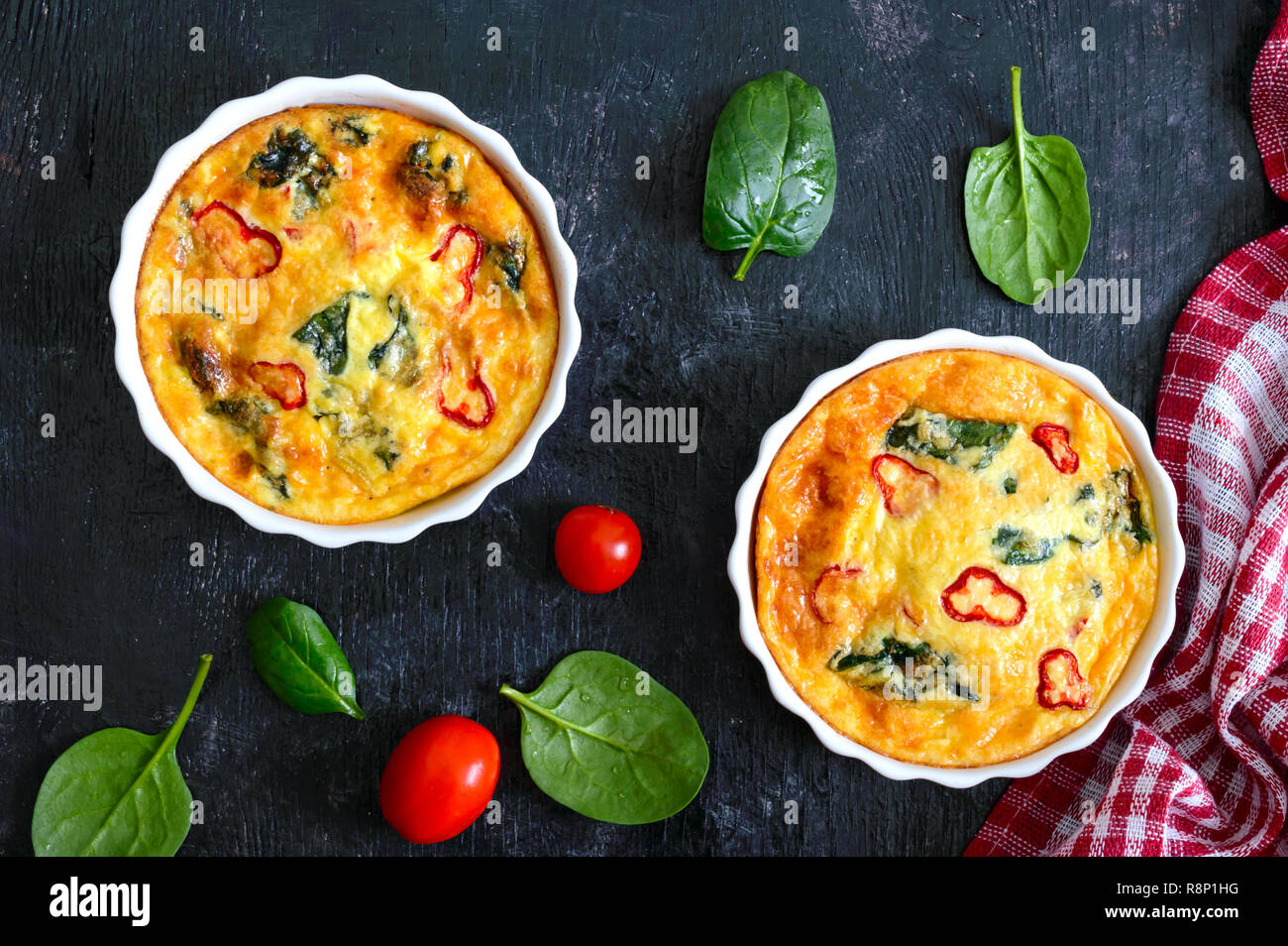Frittata with fresh vegetables and spinach. Italian omelet in ceramic forms on a black background. Top view. - Stock Image