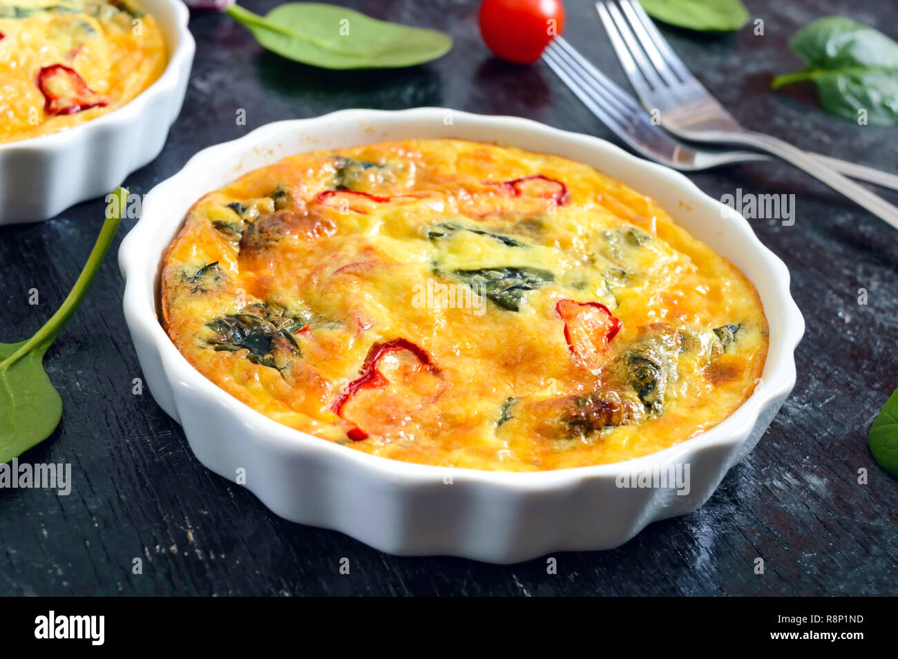 Frittata with fresh vegetables and spinach. Italian omelet in ceramic forms on a black background. - Stock Image