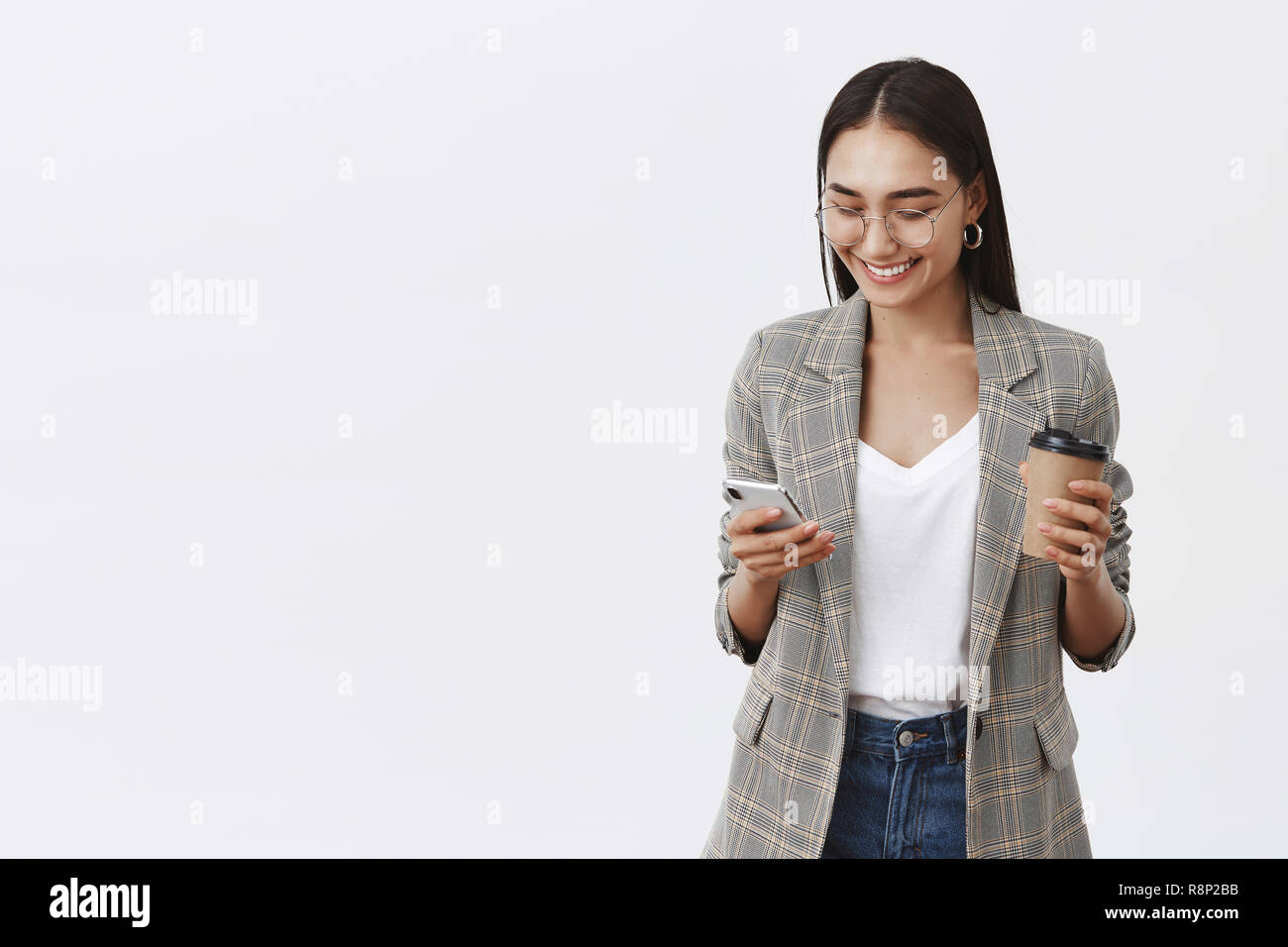 Girl checking messages, talking with friends, making new appointment. Portrait of confident busy female entrepreneur in glasses and jacket, holding cup of coffee and smartphone, using gadget - Stock Image