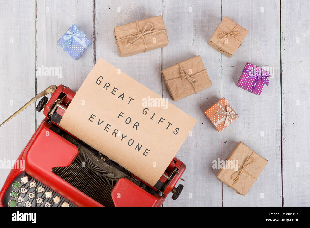 Holidays concept - red typewriter with craft paper and text 'Great gifts for everyone', gift boxes on white wooden background - Stock Image
