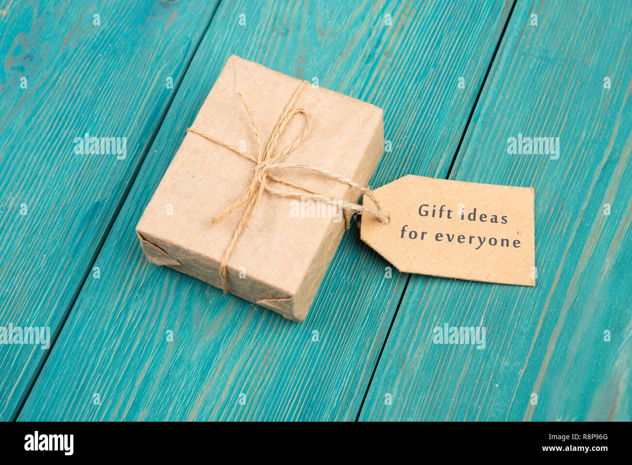 Gift box and tag with text 'Gift ideas for everyone' on blue wooden table - Stock Image