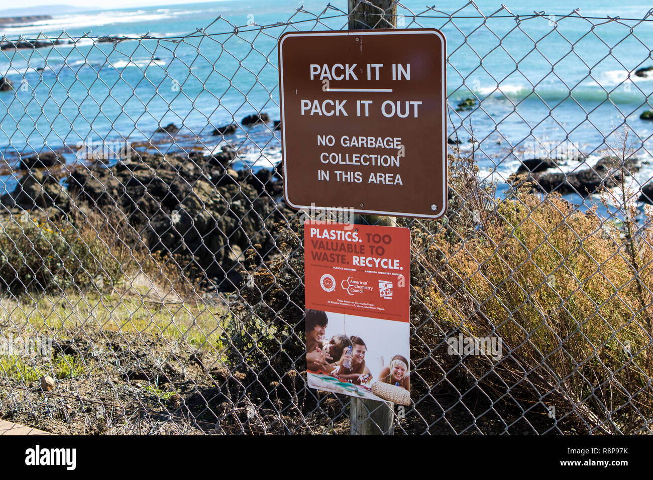 pack it in pack it out sign above a recycle plastic sign in a area along a clifftop with the ocean in the background at San Simeon, California; USA - Stock Image