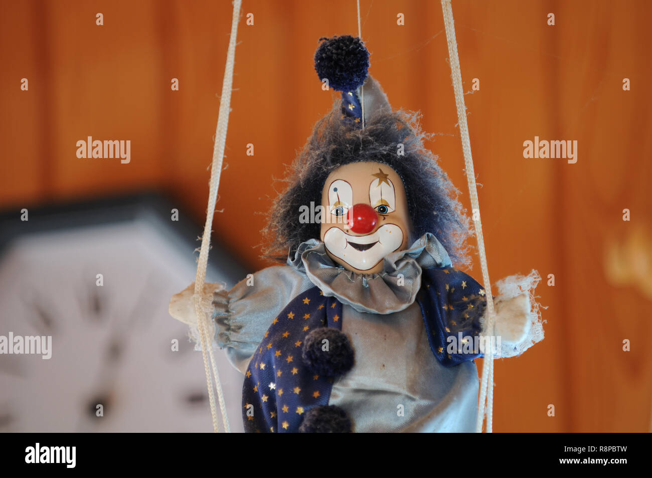 Knick-knack clown doll and clock in the background. - Stock Image
