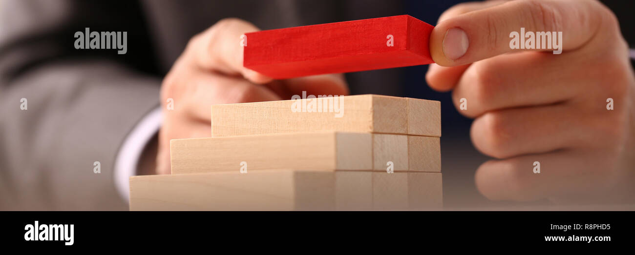 Male hand holds red wood block of stair - Stock Image